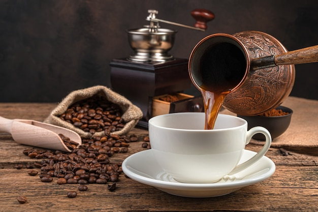 Pouring coffee into a cup of turki on a brown wall side view