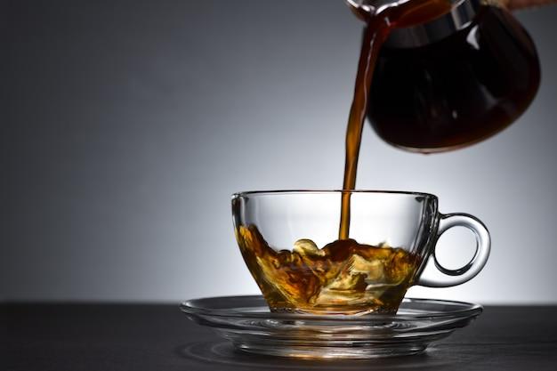 Разлива кофе на прозрачной чашке на черном фоне