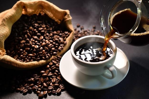 Лить кофе с дымом на чашку и кофейных зерен на мешковину на черном фоне