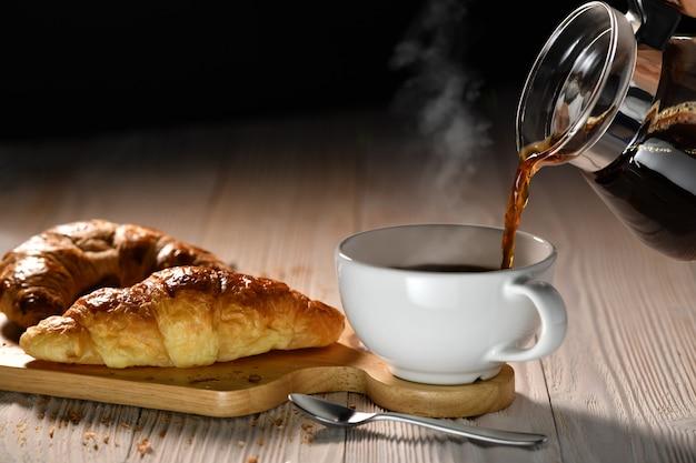 Лить кофе с дымом на чашку и круассаны на белом деревянном столе