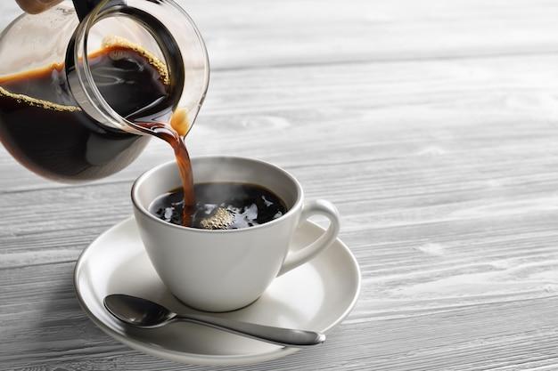Лить кофе с дымом на чашку на деревянном фоне