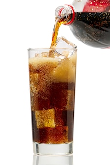 Pouring cola to glass with ice cubes