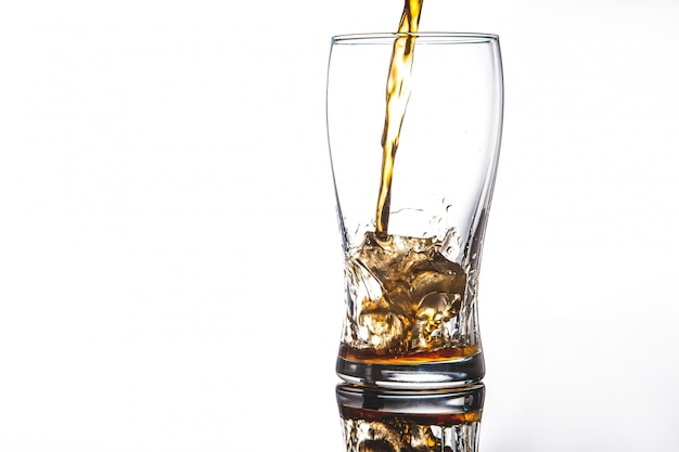Pouring cola into glass with ice on whitecopy space