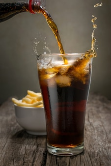 Pouring cola into the glass on wooden table with french fries background.