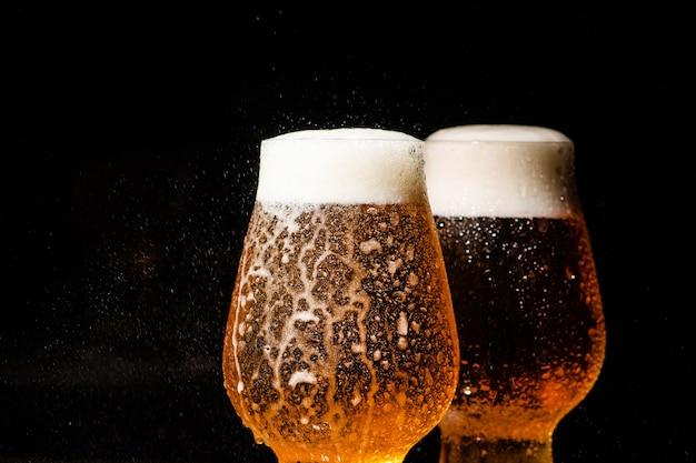 Заливка холодного пива в стакан на черном фоне