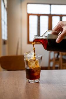 Заливка холодного кофе в стакан с кубиками льда на деревянный стол