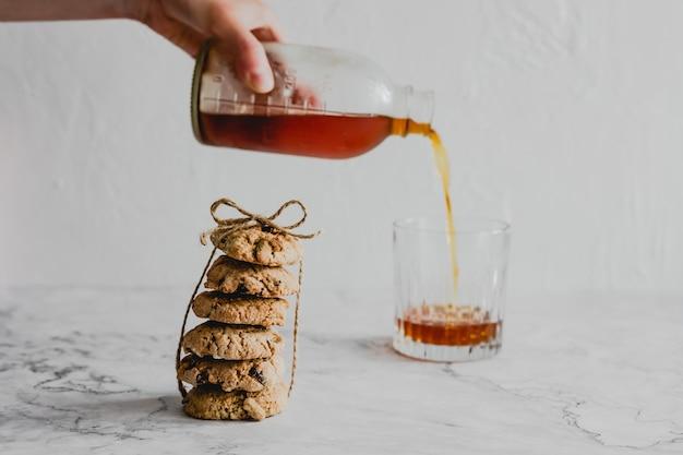Заливка холодного кофе в стакан, стопка овсяного печенья