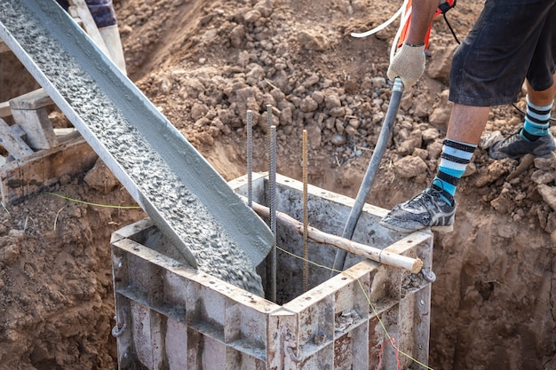 Pouring concrete into steel box for foundation pillar in process of house building