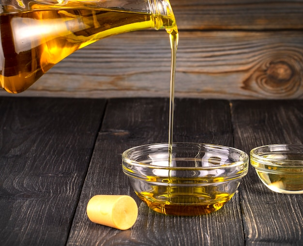 The pouring cooking oil a small glass cup on old wooden table