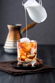 アイスコーヒーにクリームを注ぐ