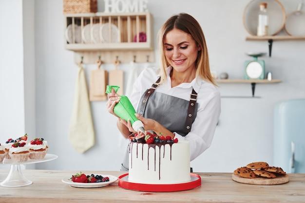 Жидкий крем. женщина стоит в помещении на кухне с домашним пирогом.