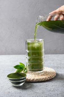유리에 해독 건강한 클로렐라 음료를 붓는 프리미엄 사진