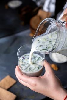 小さなガラスの中に緑のドブガを注ぐdovga若い女性を注ぐ