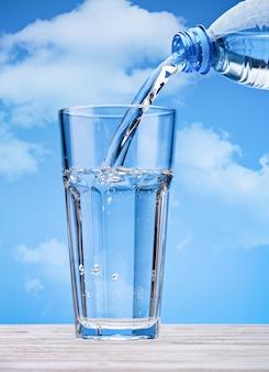 雲のある青い空を背景に、ペットボトルからガラスに飲料水を注ぐ。大きなガラスの泡でスパークリングウォーター。