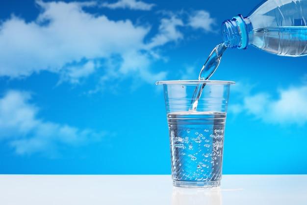 Лить питьевую воду из пластиковой бутылки в стакан, против голубого неба с облаками.