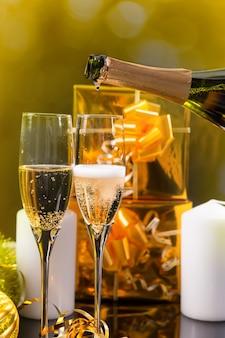 クリスマスシーズンを祝うために、ボトルから2つのスタイリッシュなフルートにお祝いのシャンパンを注ぎ、2つの金で包まれたギフトを後ろに置きます