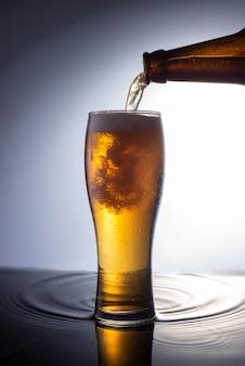 병에서 물이 있는 표면의 유리잔에 거품 맥주를 붓는다