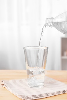 Pouring of fresh water into glass on table