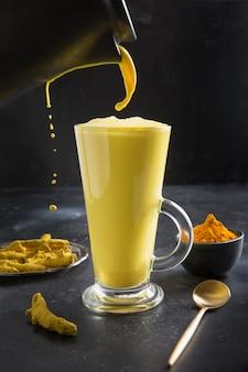 Pouring glass of ayurvedic golden turmeric latte milk with curcuma powder on black.