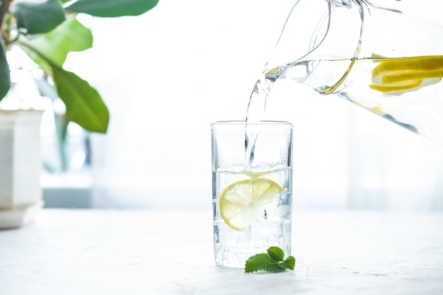 Pouring a glass of water with lemon, ice and mint on a white table