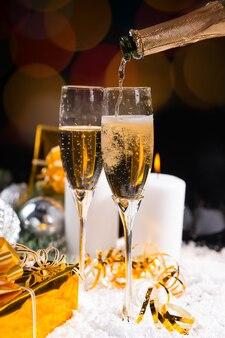冬の雪の上で燃えるろうそくと金色の贈り物でクリスマスと新年を祝うためにボトルからお祝いのシャンパンのグラスを注ぐ