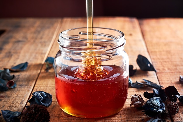 Pouring golden honey in the glass jar on wooden table