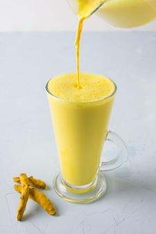 Pouring golden turmeric milk in latte glass. natural detox beverage. close up. vertical shot.