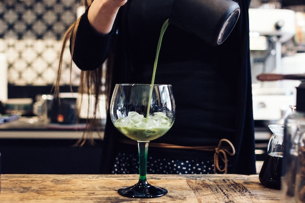 Pouring green tea matcha cocktail in a glass
