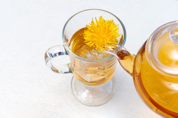 Pouring herbal dandelion tea into a transparent cup from a teapot on a white background, close-up. healthy herbal tea on hot summer days. quenching thirst. healthy food concept