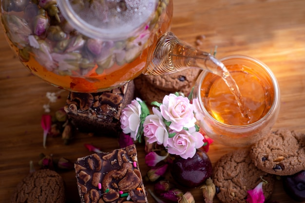 Pouring herbal tea from teapot into glass tea cup with brownie stack cake