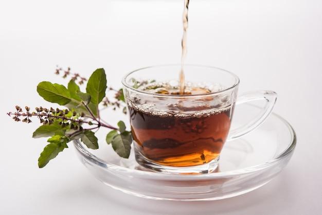 Заливка святого базилика или чая тулси в прозрачной стеклянной чашке с блюдцем на белом или черном фоне. популярная аюрведическая медицина из индии