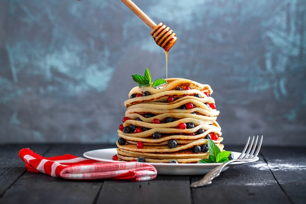 Pouring honey on golden homemade pancakes with fresh berries and mint for delicious sweet breakfast