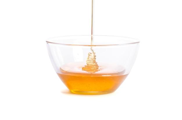 ガラスのボウルに蜂蜜を注ぐ Premium写真