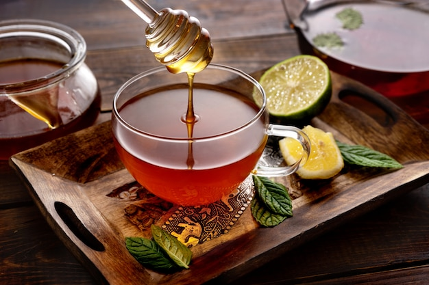 Pouring a honey into tea cup on wooden palette in rustic style