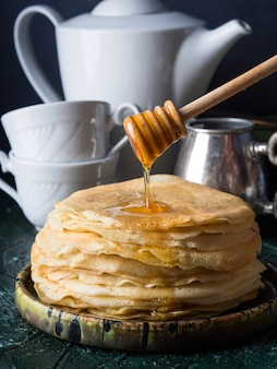 Pouring honey on stack of crepes