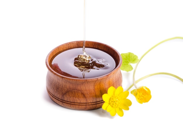 Pouring honey in the wooden bowl with yellow flowers