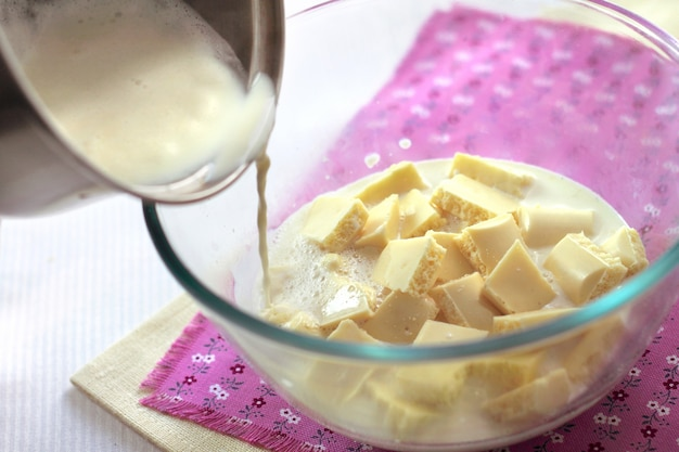 Pouring a hot cream to pieces of the white chocolate