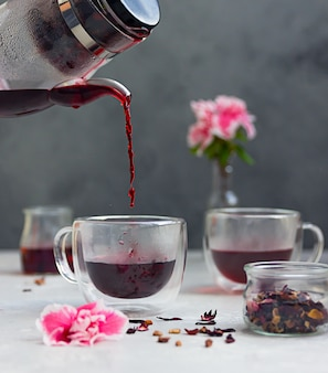 Pouring hot hibiscus tea into glass cup and pink flowers. making hibiscus tea. hot drink.
