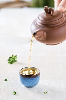 ライトテーブルのオリエンタルスタイルのカップ(ボウル)に温かい抹茶を注ぐ。カップにセレクティブフォーカス。クローズアップ、お茶会のアイデア、ミニマリズム
