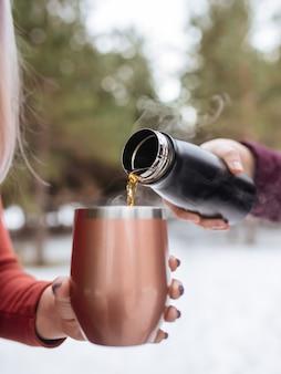 冬の森のサーモマグに熱いお茶を注ぐ