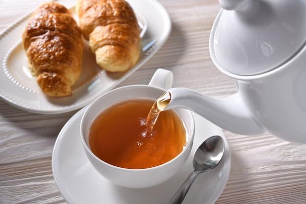 白いテーブルの背景の上にカップに熱いお茶を注ぐ