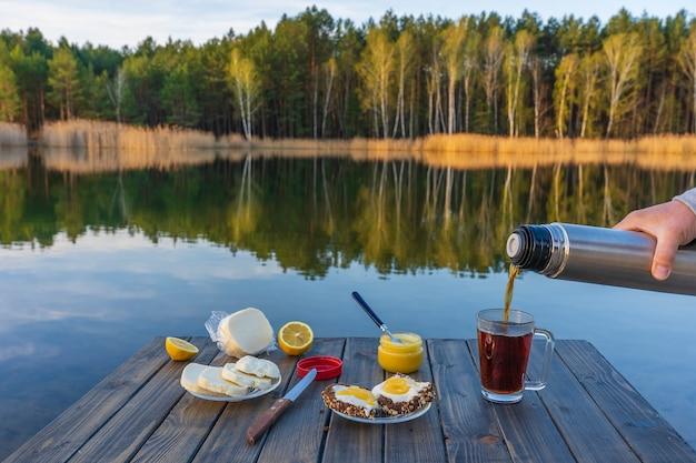 봄철에는 호수와 숲 옆에 있는 아침에 보온병에서 뜨거운 차를 유리 머그에 붓고 닫습니다. 나무 테이블에 아침 식사입니다. 자연과 여행 개념