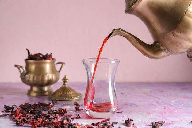 Pouring of hot tea into traditional turkish glass on table