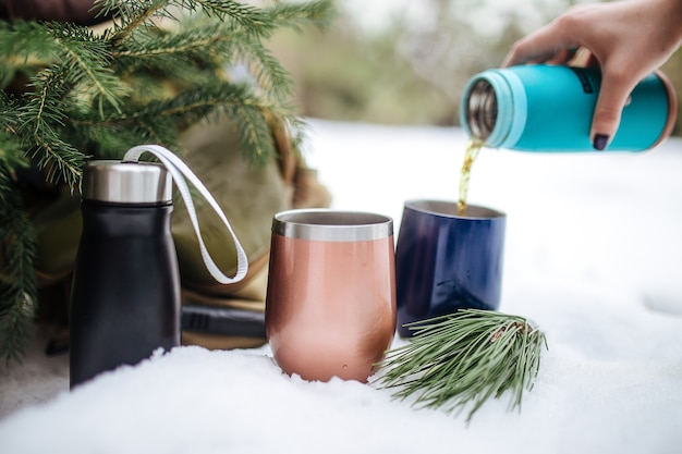 Pouring hot tea in metal thermo mugs in the snow with a spruce branches