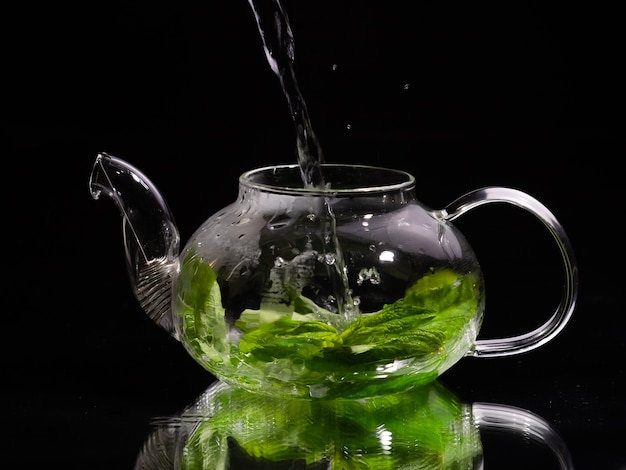 Pouring hot water into a glass teapot on a black background green mint tea herbal tea and healthy
