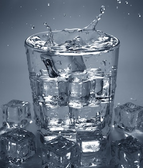 Pouring ice cube into drink glass of water. splashing of water.