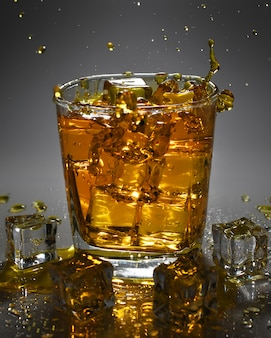 Pouring ice cube into drink glass of whiskey. splashing of whiskey.