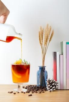 신선한 오렌지와 로즈마리 잎으로 장식된 아이스 콜드 브루 커피 혼합 오렌지 주스를 유리에 붓고 커피 타임 다과 개념.