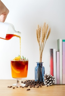 Pouring iced cold brew coffee mixed orange juice into glass, decorated with fresh orange and rosemary leaf, coffee time refreshment concept.