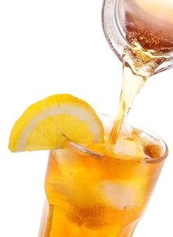 白い背景で隔離の瓶から氷とレモンと一緒にグラスにアイスティーを注ぐ